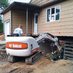 Excavating to expose the foundation walls and footings for a replacement job in Minden